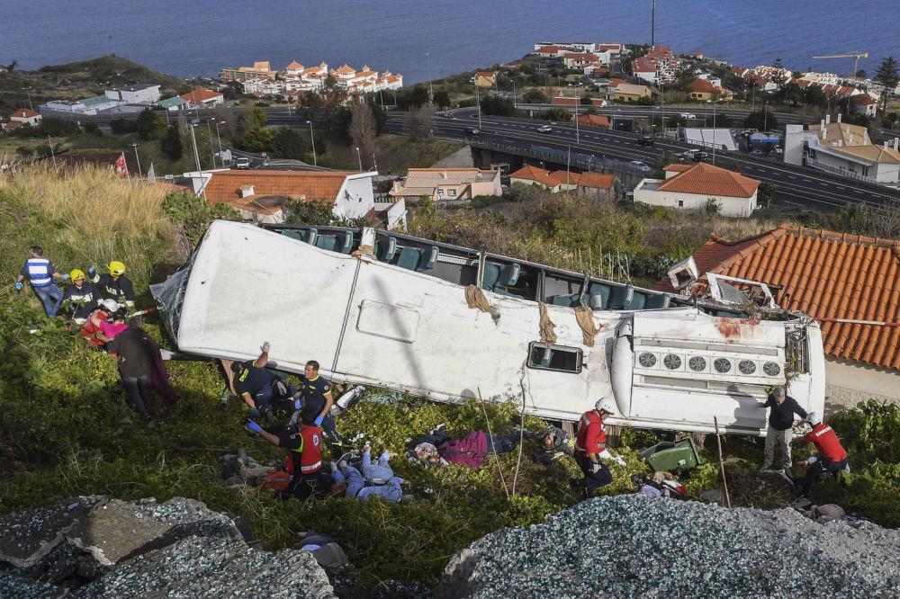 Bombeiros e equipes de resgate ao lado do ônibus turístico que se acidentou na Madeira
