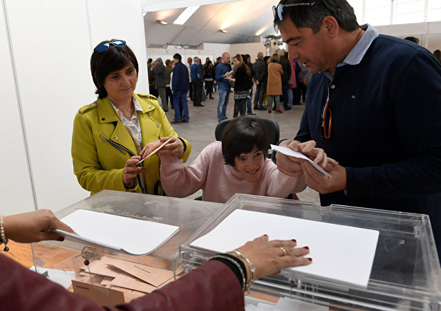 Laura Sanchez Herrero é ajudada por parentes a exercer seu direito de voto, durante a eleição geral da Espanha, em Pola de Siero, 28 de abril de 2019. Pela primeira vez na Espanha, pessoas com deficiências intelectuais têm o direito de votar.