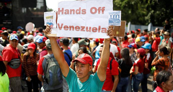 Apoiador de Nicolás Maduro com cartaz Tirem as mãos de cima da Venezuela
