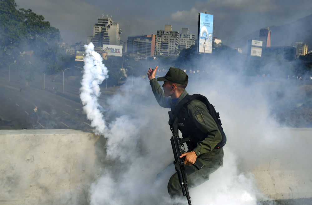 Um dos soldados apoiadores de Juan Guaidó coberto por fumaça perto da base aérea La Carlota, em Caracas