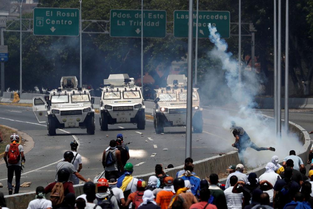 Veículos blindados das Forças Armadas da Venezuela se aproximam dos manifestantes perto da base aérea La Carlota, em Caracas