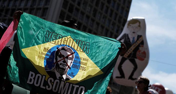 Sindicalista segura uma bandeira do Brasil com a imagem do presidente do Brasil, Bolsonaro, onde se lêvergonha, não à reforma da previdência e tire as mãos dos nossos direitos durante passeata de 1º de Maio.