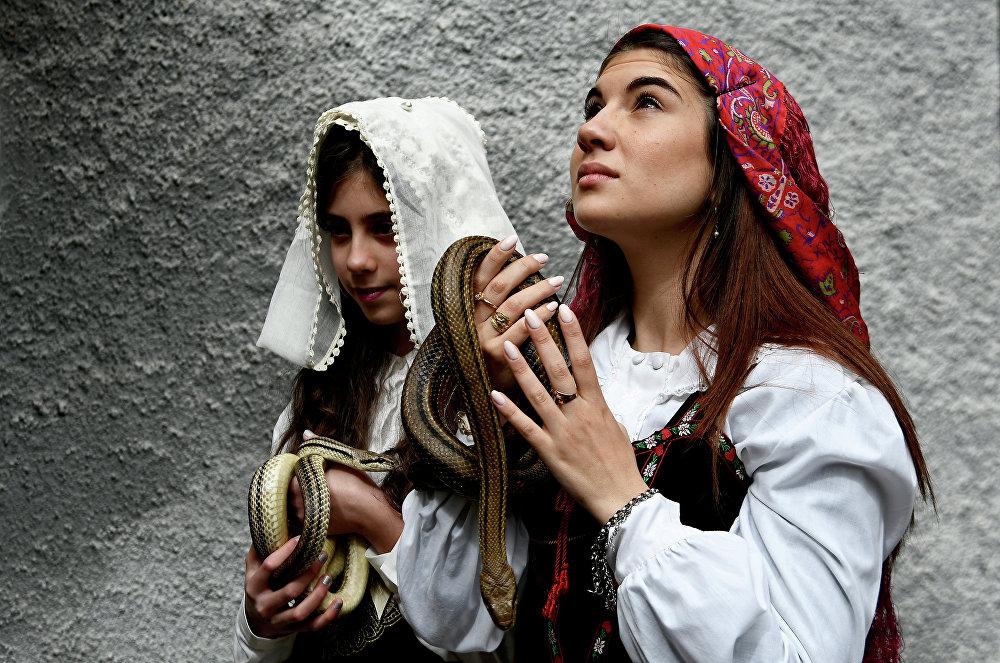Garotas segurando cobras antes de colocá-las sobre a estátua de São Domingos de Gusmão durante a procissão anual nas ruas da vila italiana de Cocullo
