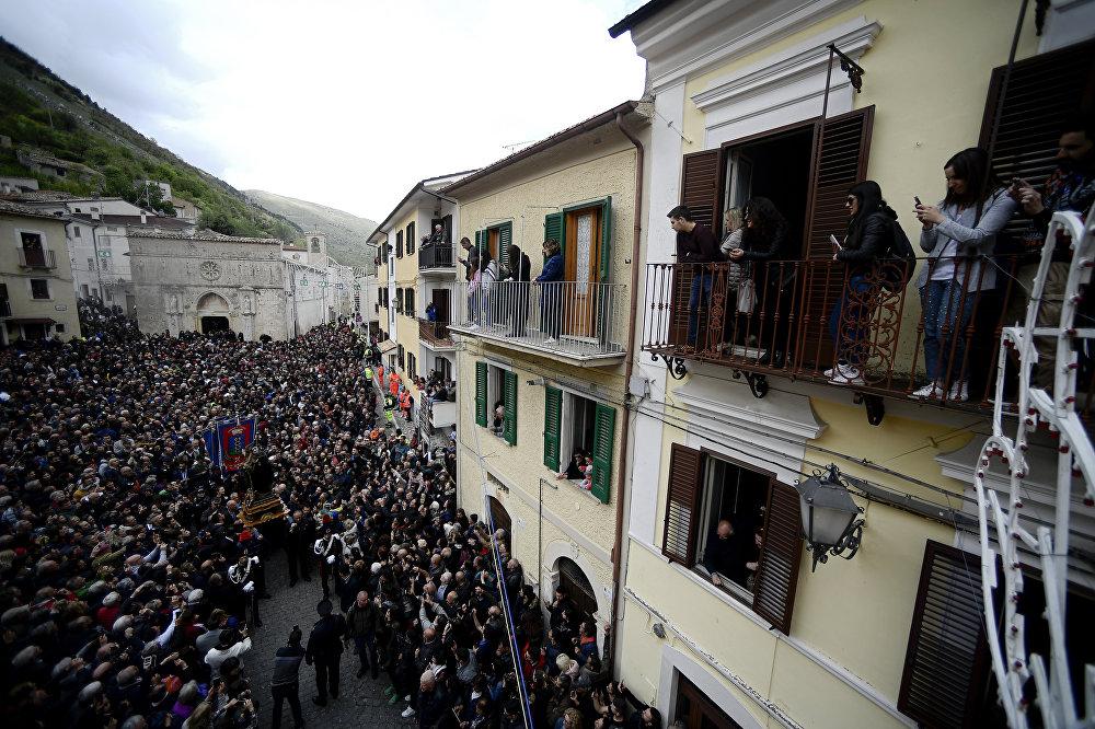 Pessoas olhando de um balcão para a estátua de São Domingos de Gusmão com cobras penduradas durante a celebração do festival dos Serpari na vila italiana de Cocullo