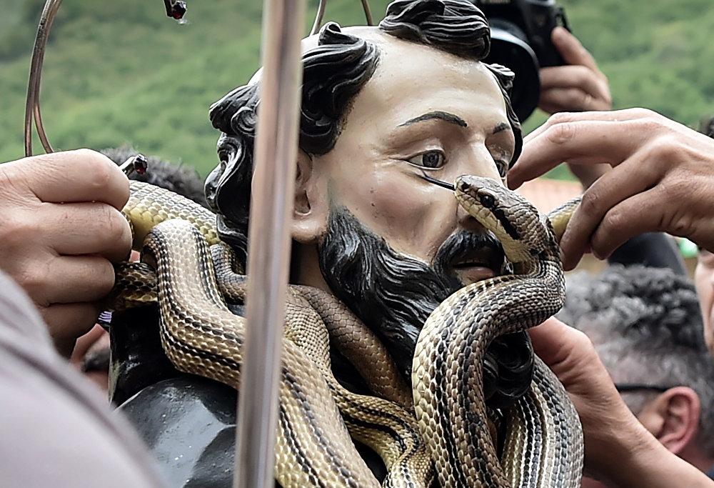 Pessoas retirando as cobras da estátua de São Domingos de Gusmão durante a celebração do festival anual dos Serpari nas ruas da vila italiana de Cocullo