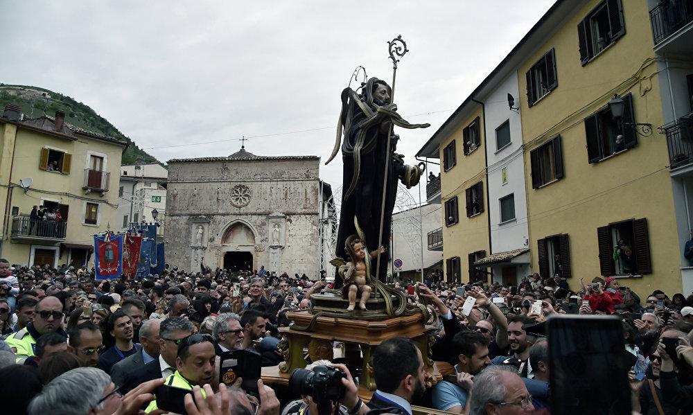 Pessoas segurando a estátua de São Domingos de Gusmão coberta de cobras no decorrer da celebração do festival dos Serpari nas ruas da vila italiana de Cocullo