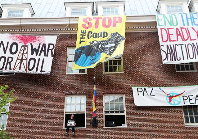 Um ativista em oposição ao envolvimento dos EUA na Venezuela que ocupa a embaixada venezuelana, senta-se em um peitoril da janela em Washington, EUA.