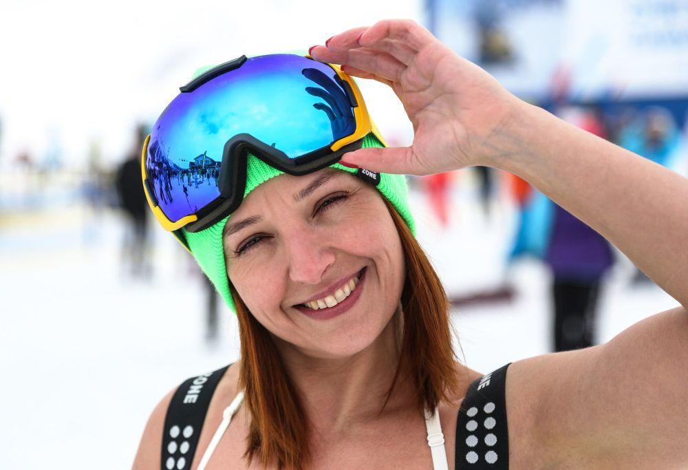 Mulher posa para foto com óculos de proteção esportivos durante o festival na neve Khibiny-Bikini 2019, em Kirovsk, na região russa de Murmansk