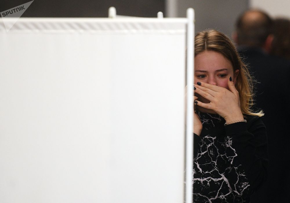 Jovem chora perto do quarto de apoio psicológico organizado para parentes e passageiros das vítimas do acidente com Sukhoi Superjet 100
