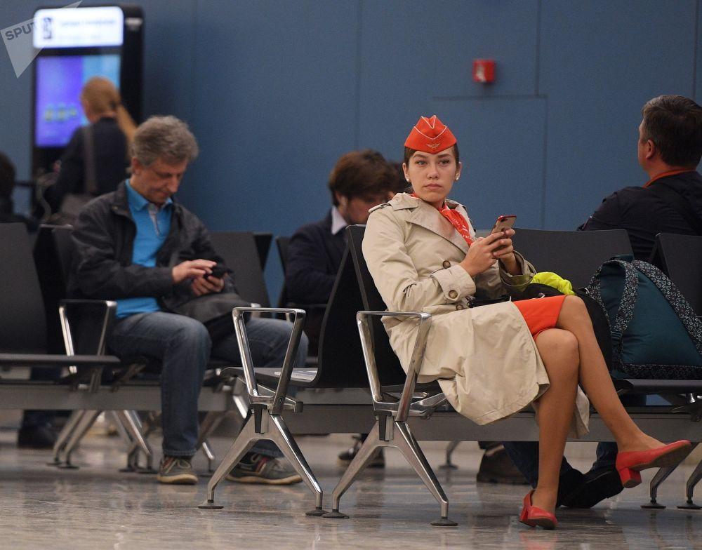 Passageiros e tripulantes sentados na sala de espera no Aeroporto Sheremetyevo, perto de Moscou