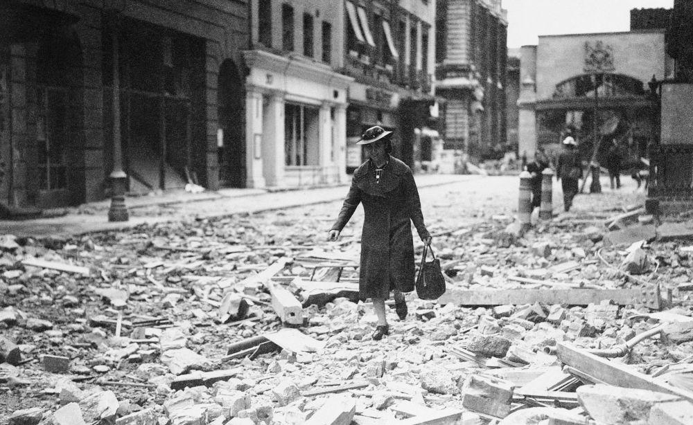 Uma mulher passa por uma das ruas de Londres, destruída após ataques aéreos