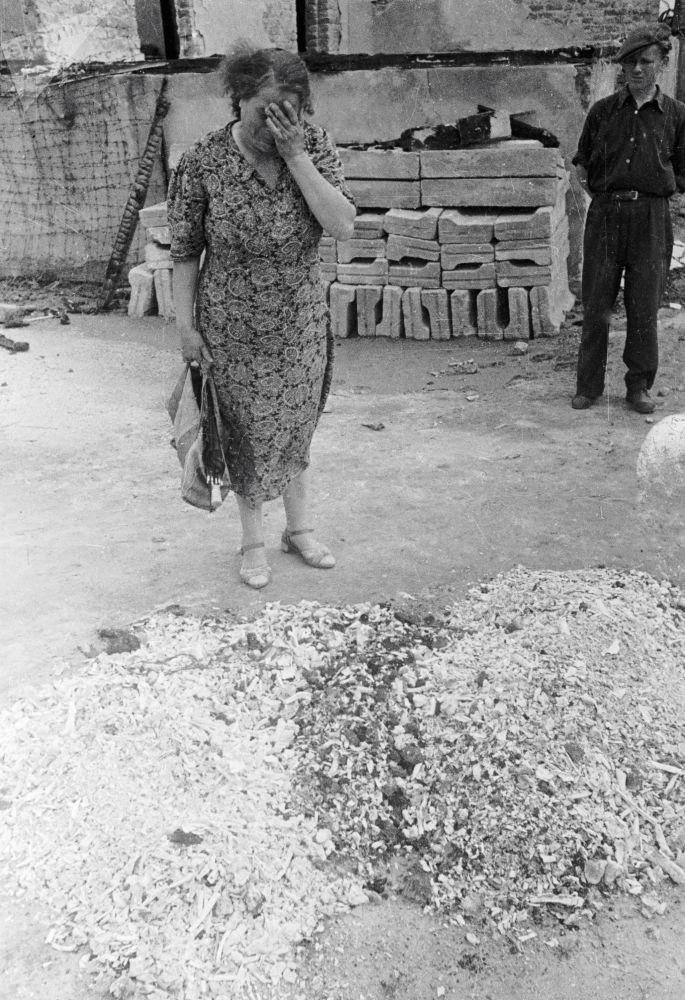 Mulher chora sobre cinzas de pessoas queimadas no campo de concentração alemão nazista Majdanek, Polônia