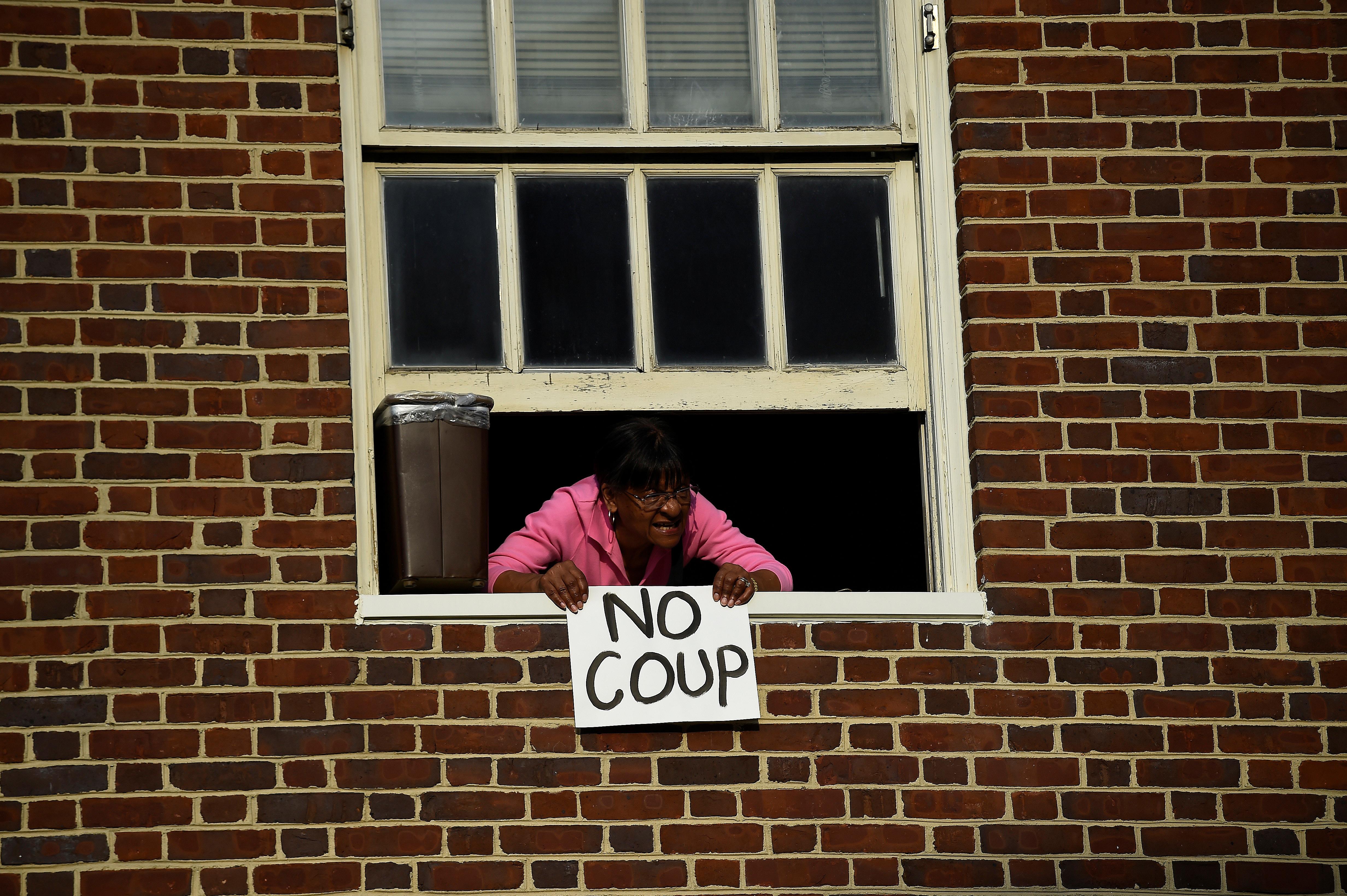 Mulher segura cartaz em que diz Sem golpe em apoio a Maduro da janela de embaixada venezuelana, 1º de maio de 2019