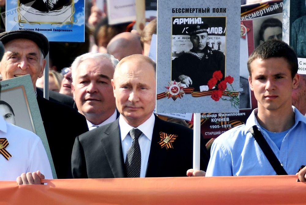 O presidente russo, Vladimir Putin, com um retrato do seu pai, veterano de guerra, durante a marcha do Regimento Imortal dedicada ao Dia da Vitória