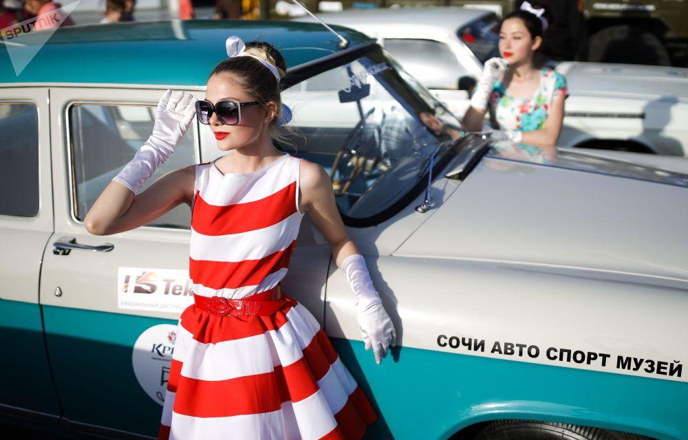 Menina posa ao lado de um carro Volga GAZ-21 desenvolvido em 1956 na União Soviética