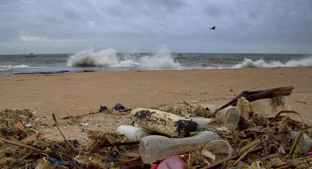 Uma garrafa plástica e outros detritos em praia do Oceano Índico localizada em Uswetakeiyawa, Sri Lanka.