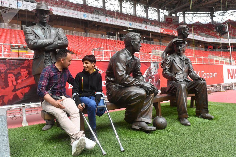 Herói da fotografia Desejo de Viver posa ao lado de estátua no estádio do Spartak de Moscou