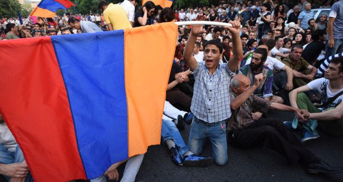 Manifestantes acenando as bandeiras nacionais durante um protesto contra o aumento das tarifas de energia em Erevan, capital da Armênia, em 22 de junho de 2015.