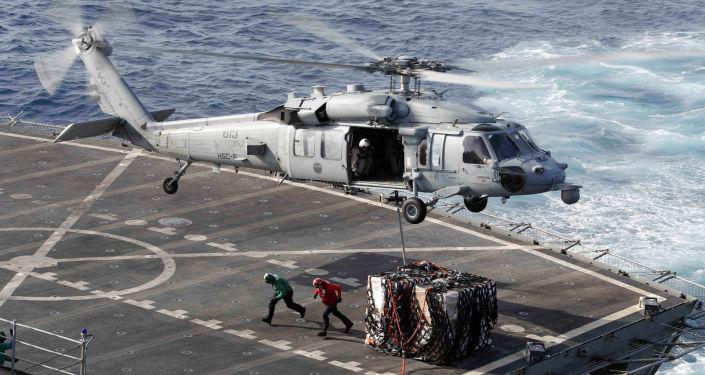Helicóptero Sea Hawk transportando carga, em 19 de maio de 2019