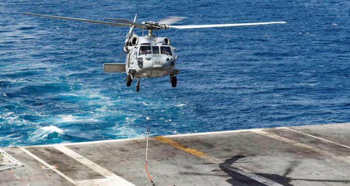 Helicóptero Sea Hawk transportando carga do navio de apoio USNS Arctic (T-AOE 8) para o porta-aviões norte-americano USS Abraham Lincoln durante um reabastecimento no mar Arábico, em 19 de maio de 2019