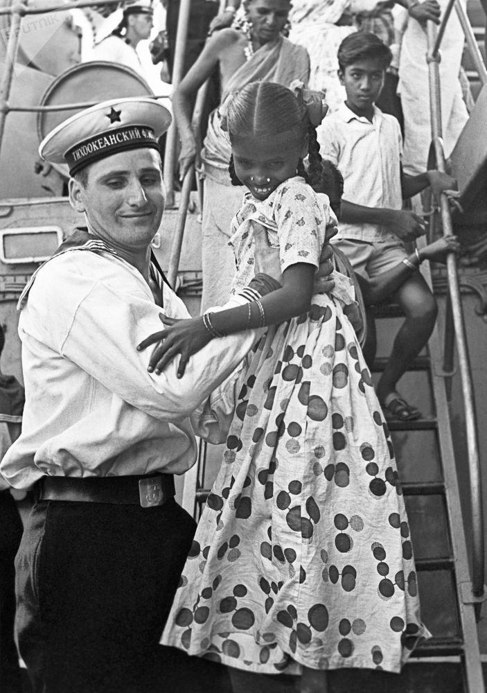Marinheiro soviético recebe crianças indianas na coberta do navio durante a visita da Frota do Pacifico à Índia, 1968