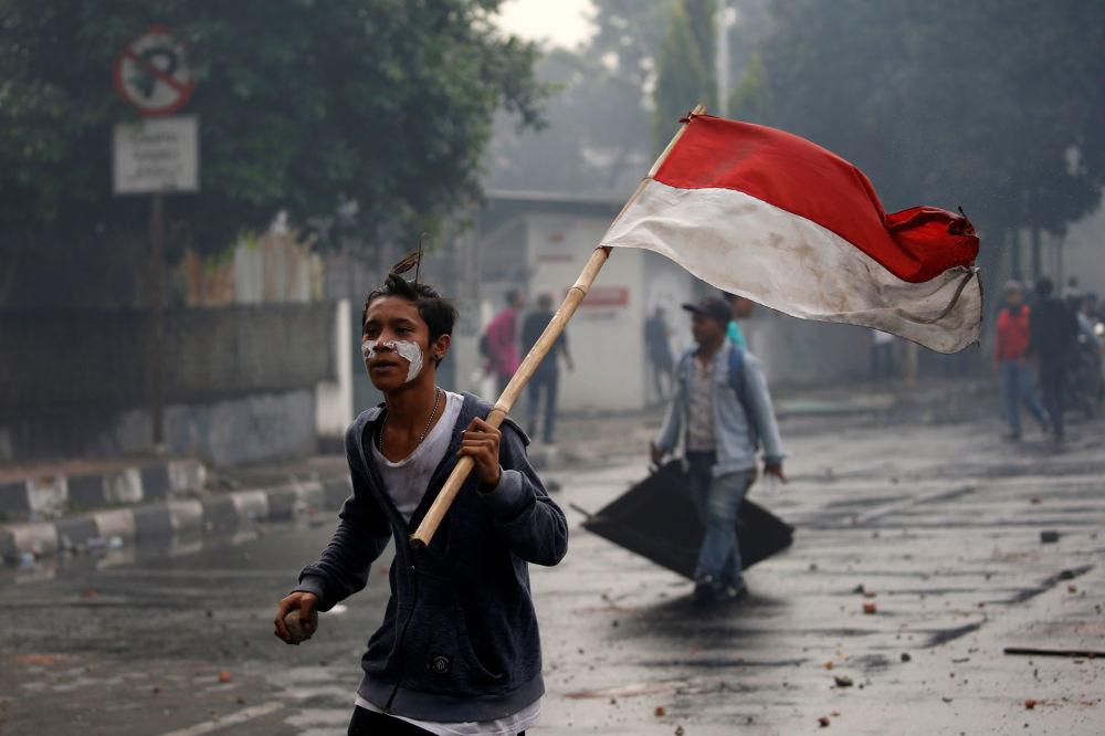 Manifestante carrega bandeira nacional da Indonésia durante protesto após anúncio dos resultados oficiais das eleições, em Jacarta, Indonésia, 22 de maio de 2019