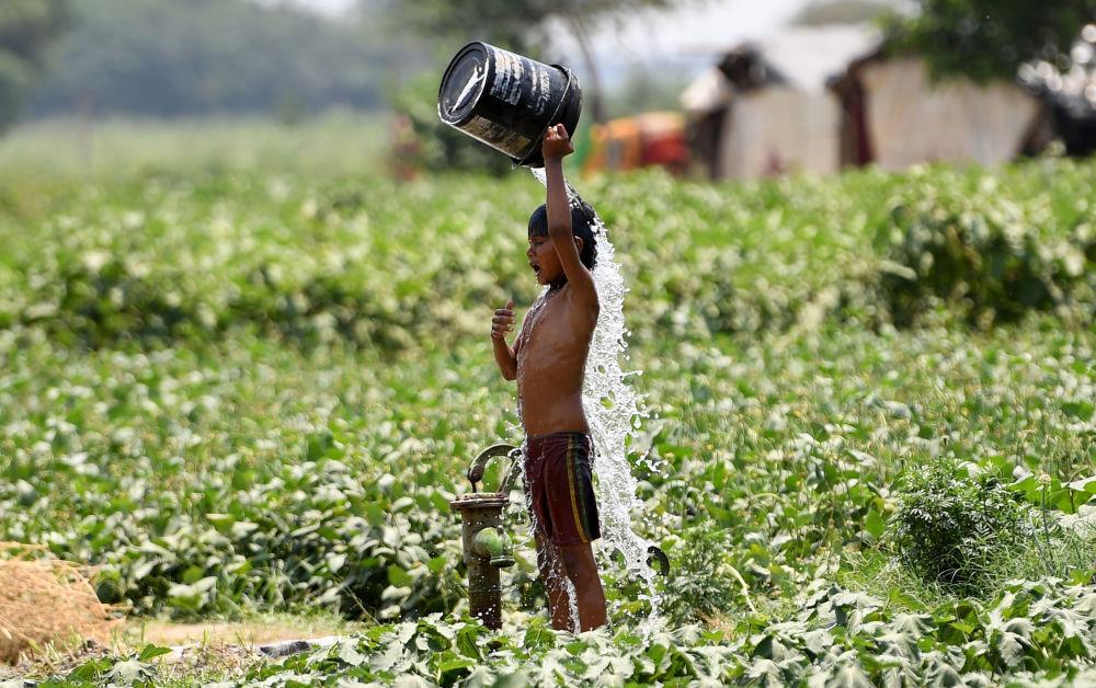 Menino se refresca com água nos dias quentes em Nova Deli, Índia
