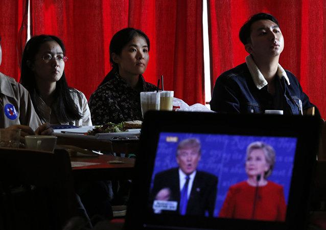 Estudantes chineses assistem a transmissão ao vivo do debate presidencial entre a candidata democrata Hillary Clinton e o candidato republicano à presidência, Donald Trump, em um café em Pequim.
