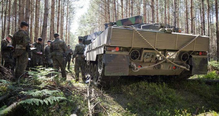 Militares e um veículo blindado nos exercícios militares Noble Jump 19