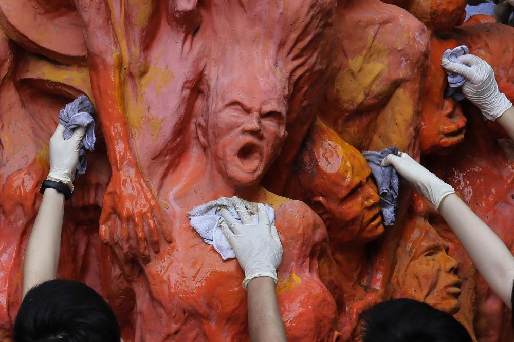 Estudantes da Universidade de Hong Kong limpam a estátua do Pilar da Vergonha, um memorial aos mortos na repressão de Tiananmen em 1989