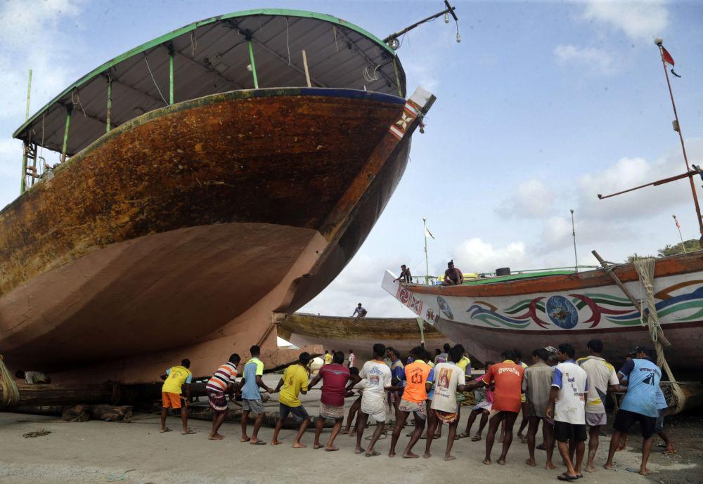 Pescadores indianos puxam navio para terra antes do início da estação das monções