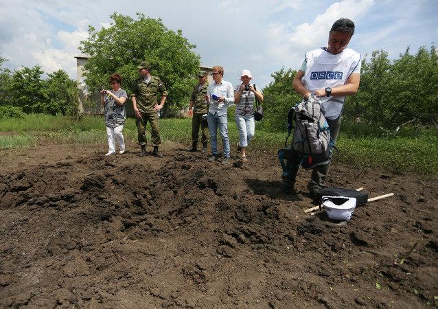 Membro da missão da OSCE e jornalistas examinam cratera em Telmanove, ao sul de Donetsk, após bombardeios das tropas ucranianas