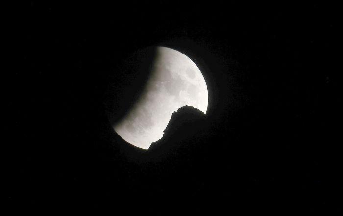 Eclipse lunar parcial visto atrás de pico nos Alpes suíços