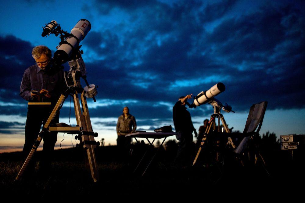 Pessoas aguardam o eclipse lunar parcial com seus telescópios em Viena
