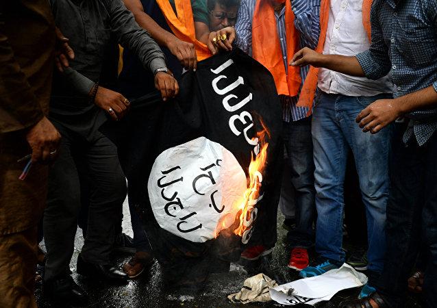 Ativistas do grupo indiano Hindu Sena, da direita, queimam uma bandeira do grupo jihadista Daesh, o autoproclamado Estado Islâmico, em Nova Deli, Índia