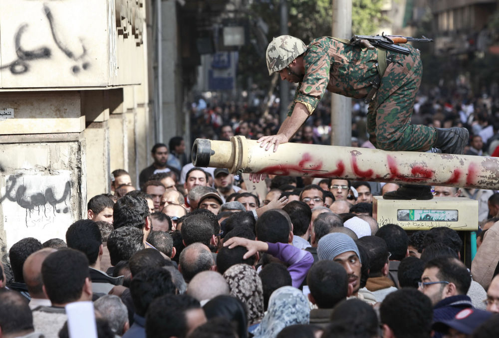 Militar fala com manifestantes na praça Tahrir, Cairo