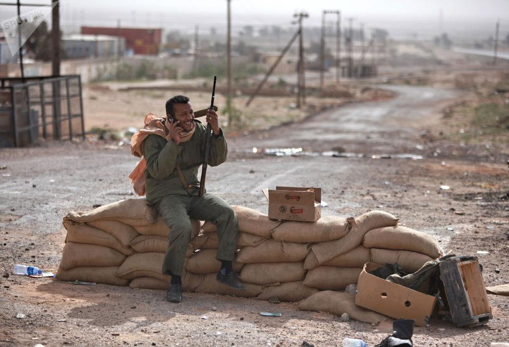 Militante armado fala pelo celular no posto de controle na cidade de Brega, situada no leste da Líbia e controlada pelos rebeldes