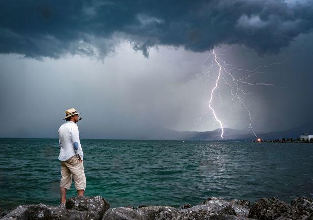Homem e relâmpago ao fundo no lago de Genebra, na Suíça