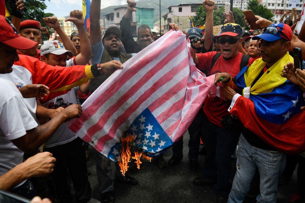 Apoiadores do governo venezuelano queimam bandeira estadunidense durante a manifestação contra as sanções dos EUA em Caracas