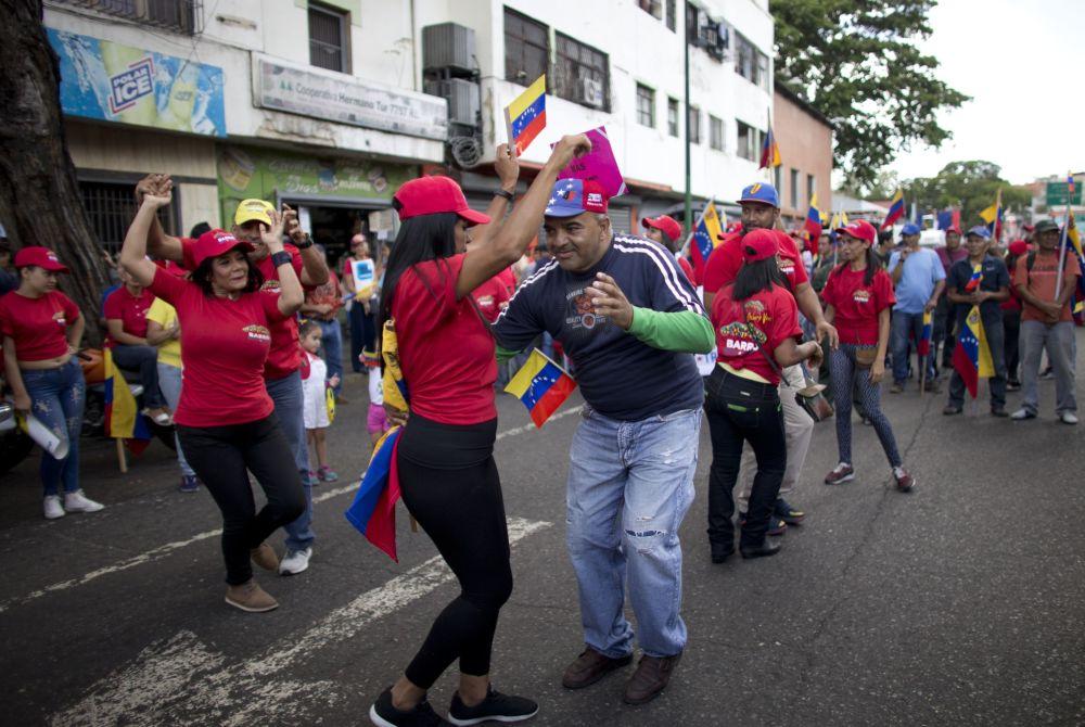 Apoiadores do governo de Maduro dançam durante a manifestação contra o bloqueio econômico imposto pelos EUA