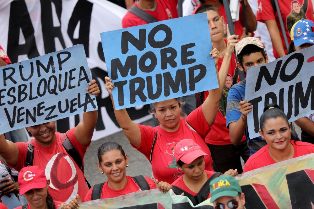 Apoiadores do governo da Venezuela empunhando cartazes contra o presidente dos EUA, Donald Trump, durante o protesto contra as sanções norte-americanas