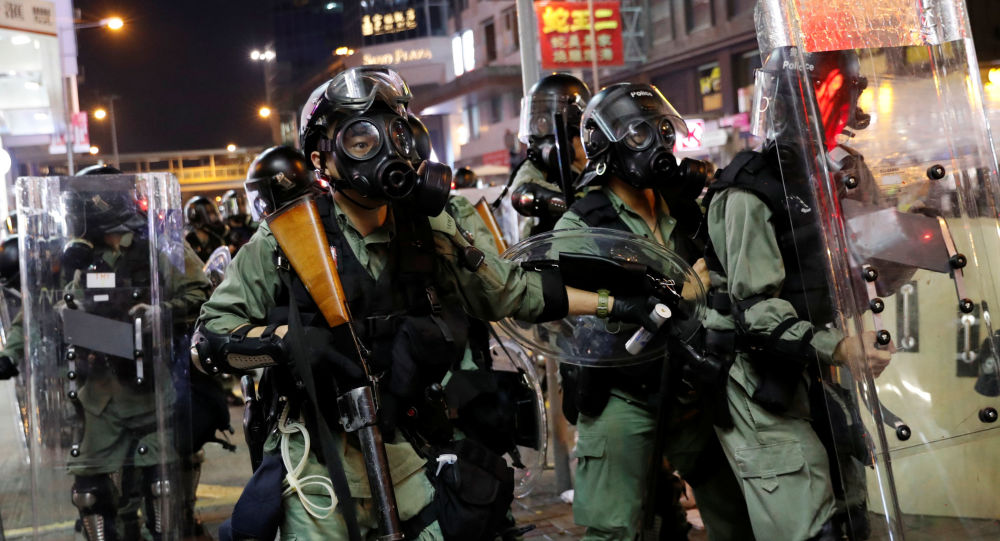 Policiais avançam em direção a manifestantes em Hong Kong, China