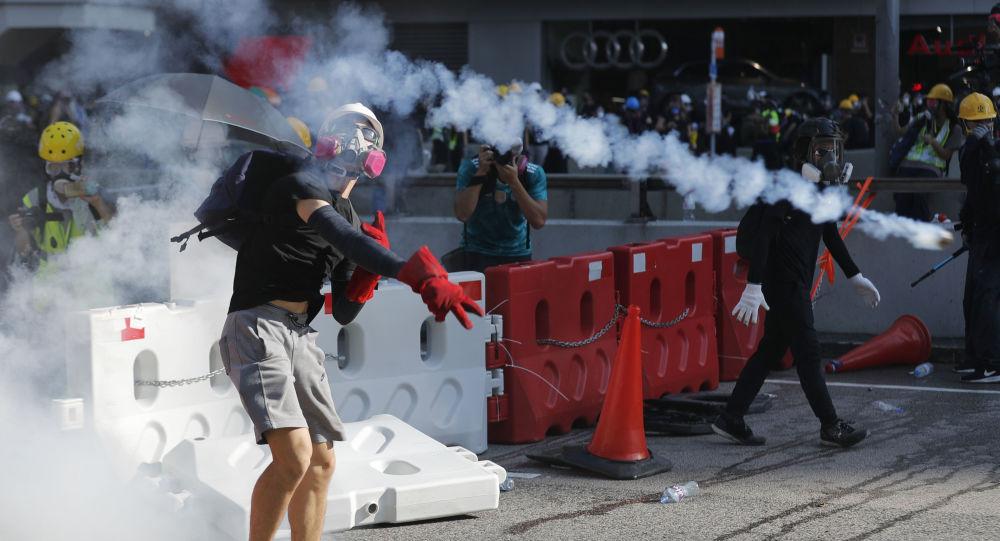 Manifestantes  repelem tubos de gás lacrimogênito durante protestos em Hong Kong
