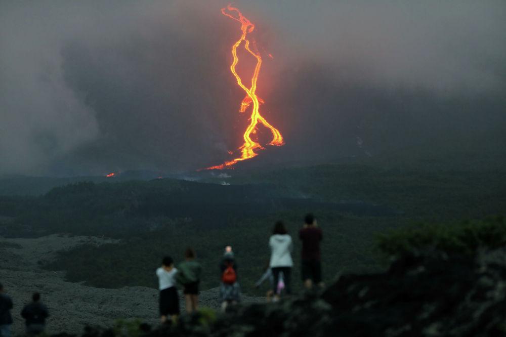 Pessoas olhando a erupção do vulcão Piton de la Fournaise na ilha francesa de Reunião