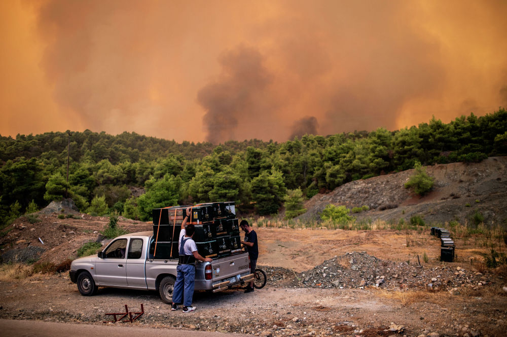 Fazendeiros durante incêndio florestal na ilha de Eubeia, Grécia