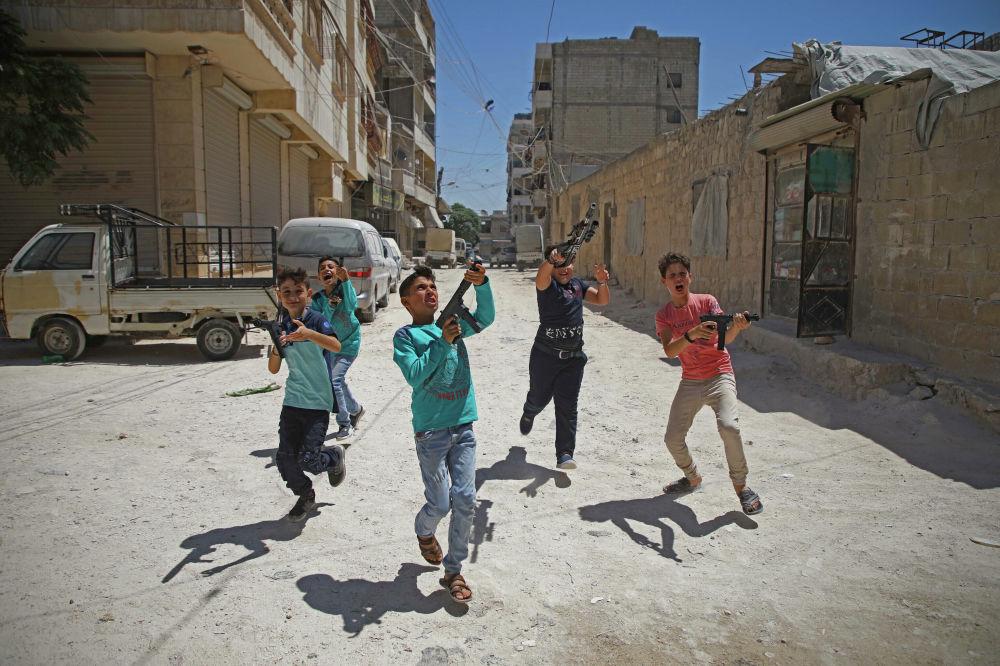 Crianças brincando com fuzis de plástico em Idlib, Síria