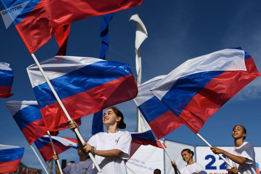 Meninas com bandeiras da Rússia na praça Karl Marx na cidade de Novosibirsk, na Rússia