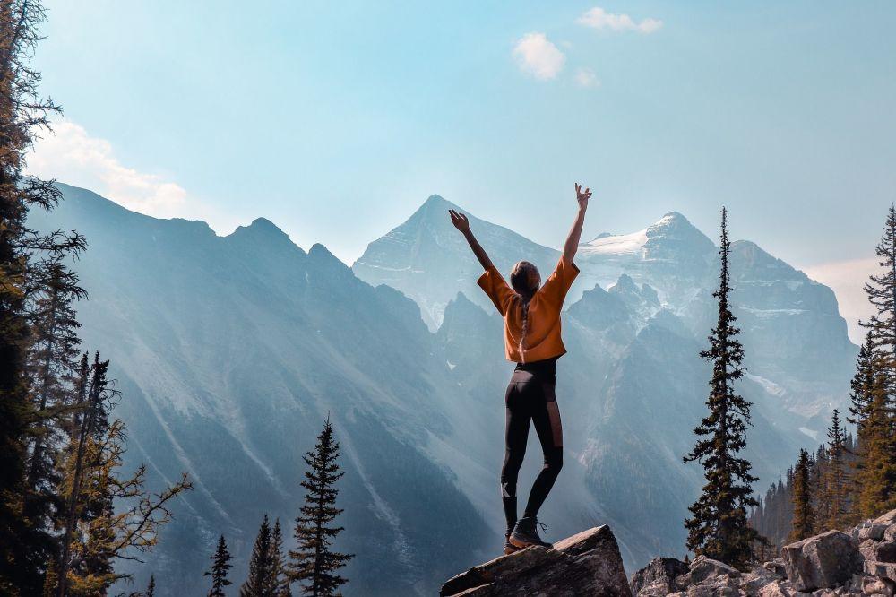 Garota posa com montanhas canadenses ao fundo