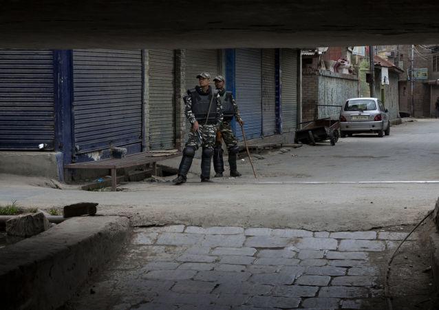 Soldados paramilitares indianos vigiam um mercado fechado no centro de Srinagar, na Caxemira controlada pela Índia, em 27 de agosto de 2019