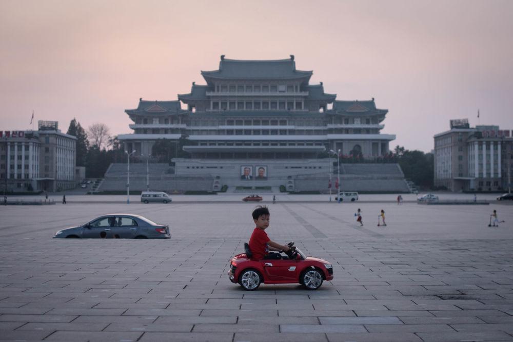Menino em carro de brinquedo na praça de Kim Il-sung em Pyongyang, na Coreia do Norte